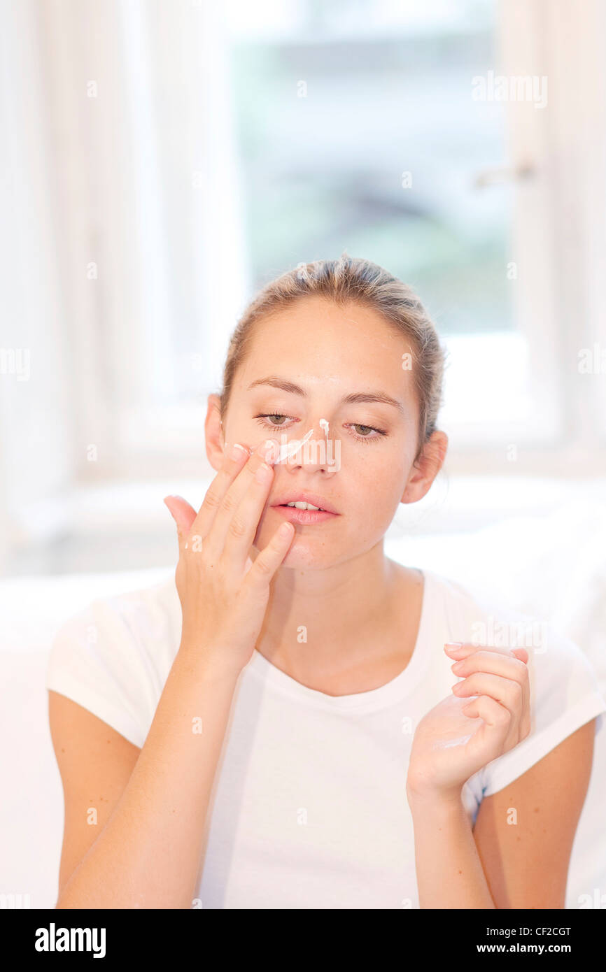 Female highlighted fair hair off her face, wearing a white t shirt, applying face cream to her nose, unsmiling, - Stock Image