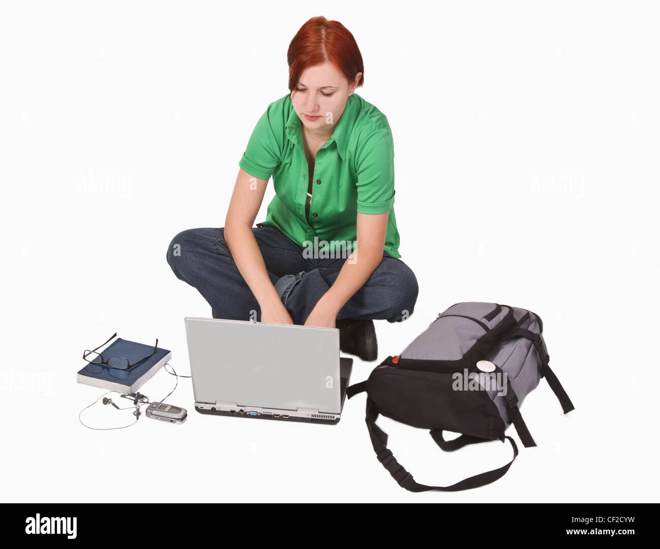 Redheaded teenage girl with a lot of items around her working on a laptop. - Stock Image