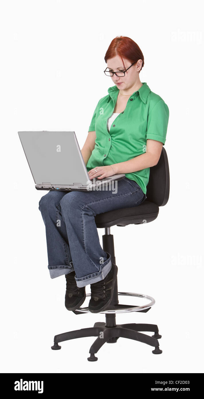Redheaded teenager sitting on a high chair and working on a laptop. - Stock Image