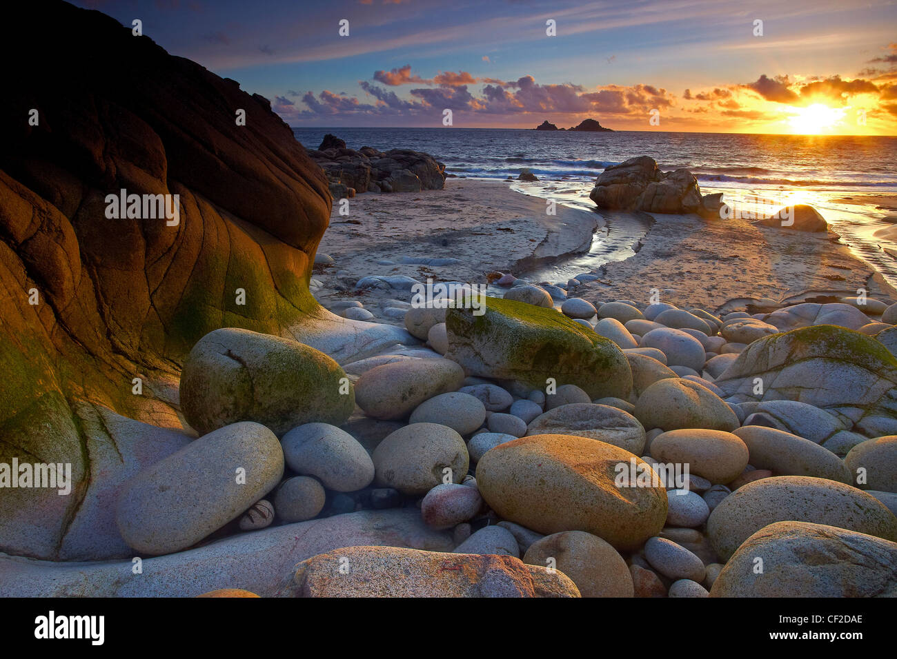 Sunset at Porth Nanven, known locally as Dinosaur Egg Beach due to the large number of ovoid rocks found there. - Stock Image