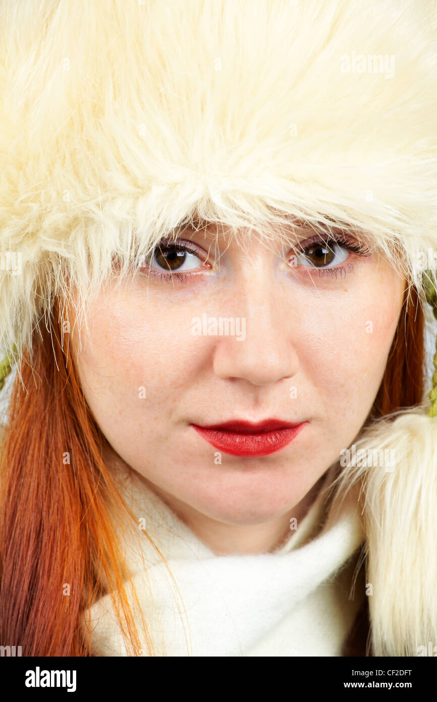 Headshot of an elegant 20 year old redhead wearing a furry hat. - Stock Image