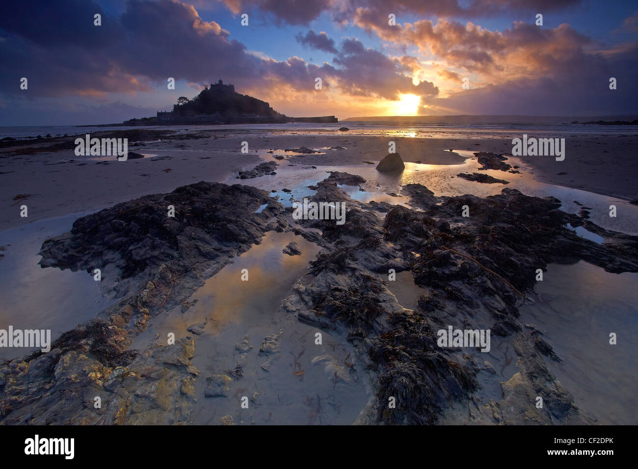 Sunset over St Michaels Mount in Mount's Bay from the beach at Marazion. - Stock Image