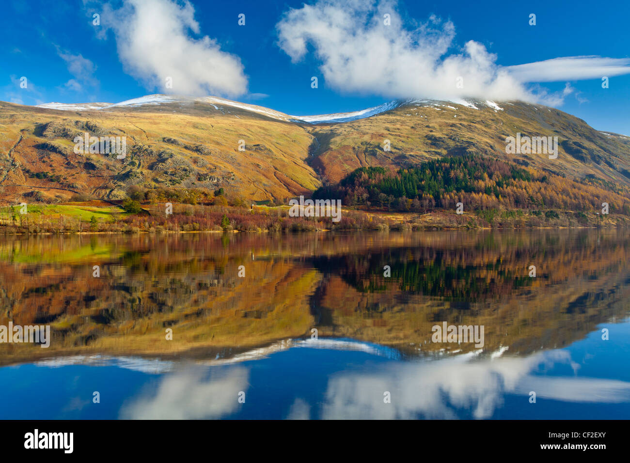 Lakeland hills reflected upon the still face of the Thirlmere Reservoir in the Lake District National Park. - Stock Image