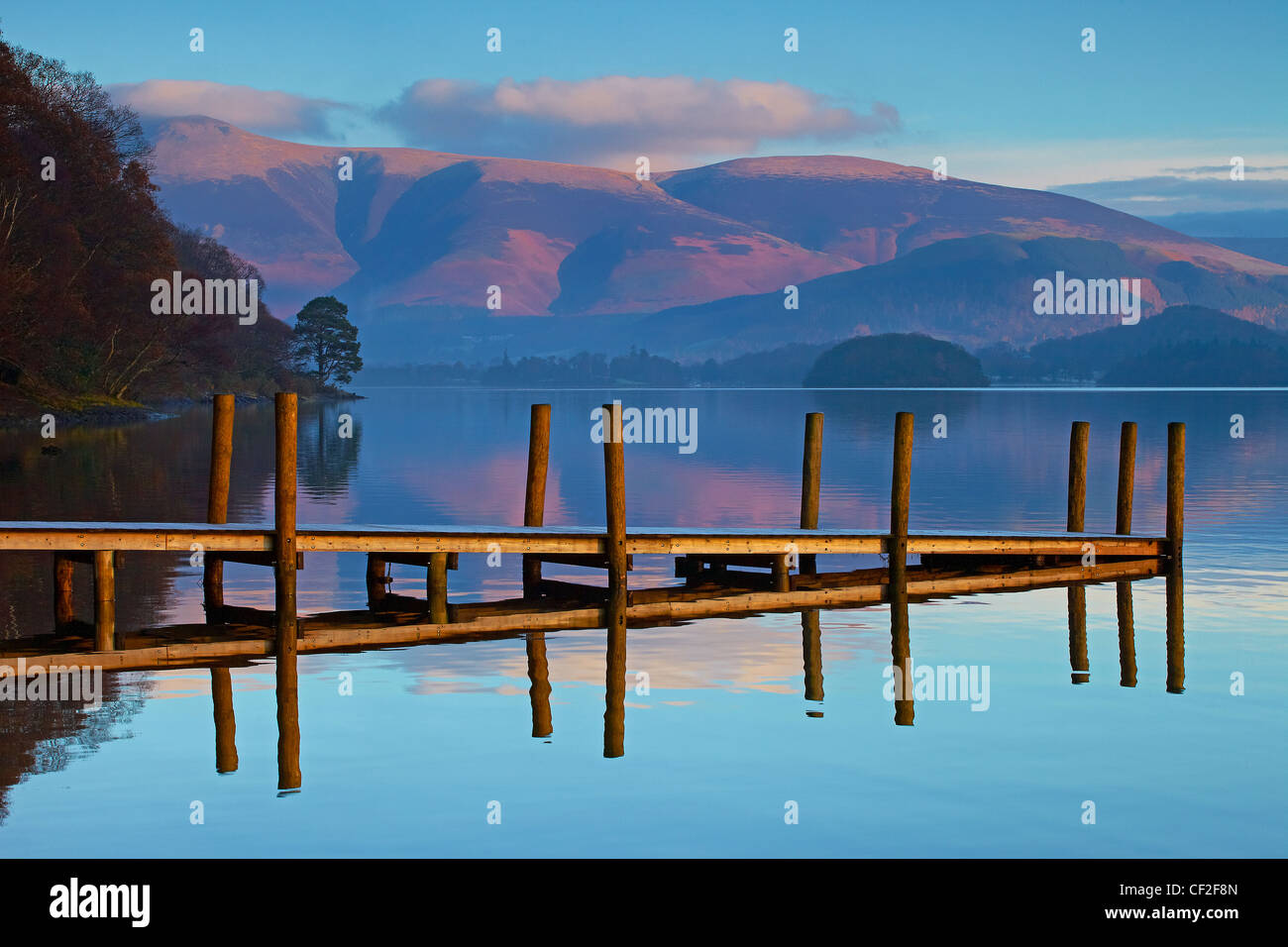 Brandelhow Jetty reflected in the still water of Derwentwater in the Lake District National Park. - Stock Image