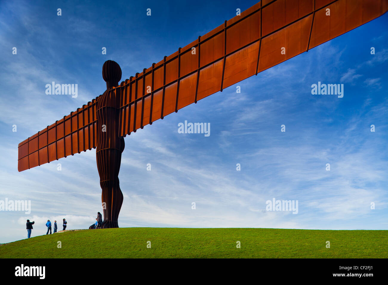 Tourists standing under the iconic Angel of the North statue by Antony Gormley. The 'Angel', built on a - Stock Image