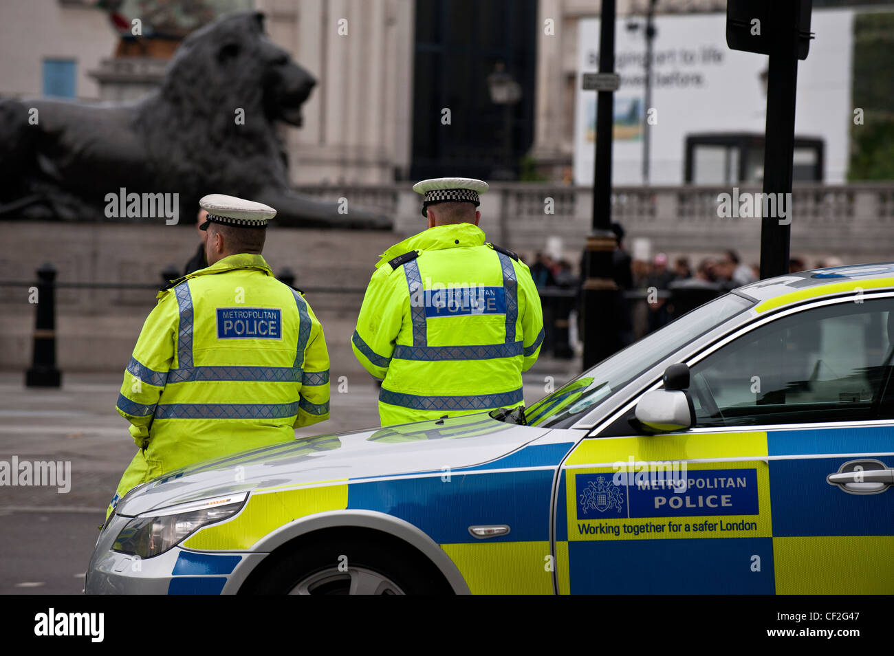 Metropolitan Police officers and car on duty in central London. - Stock Image