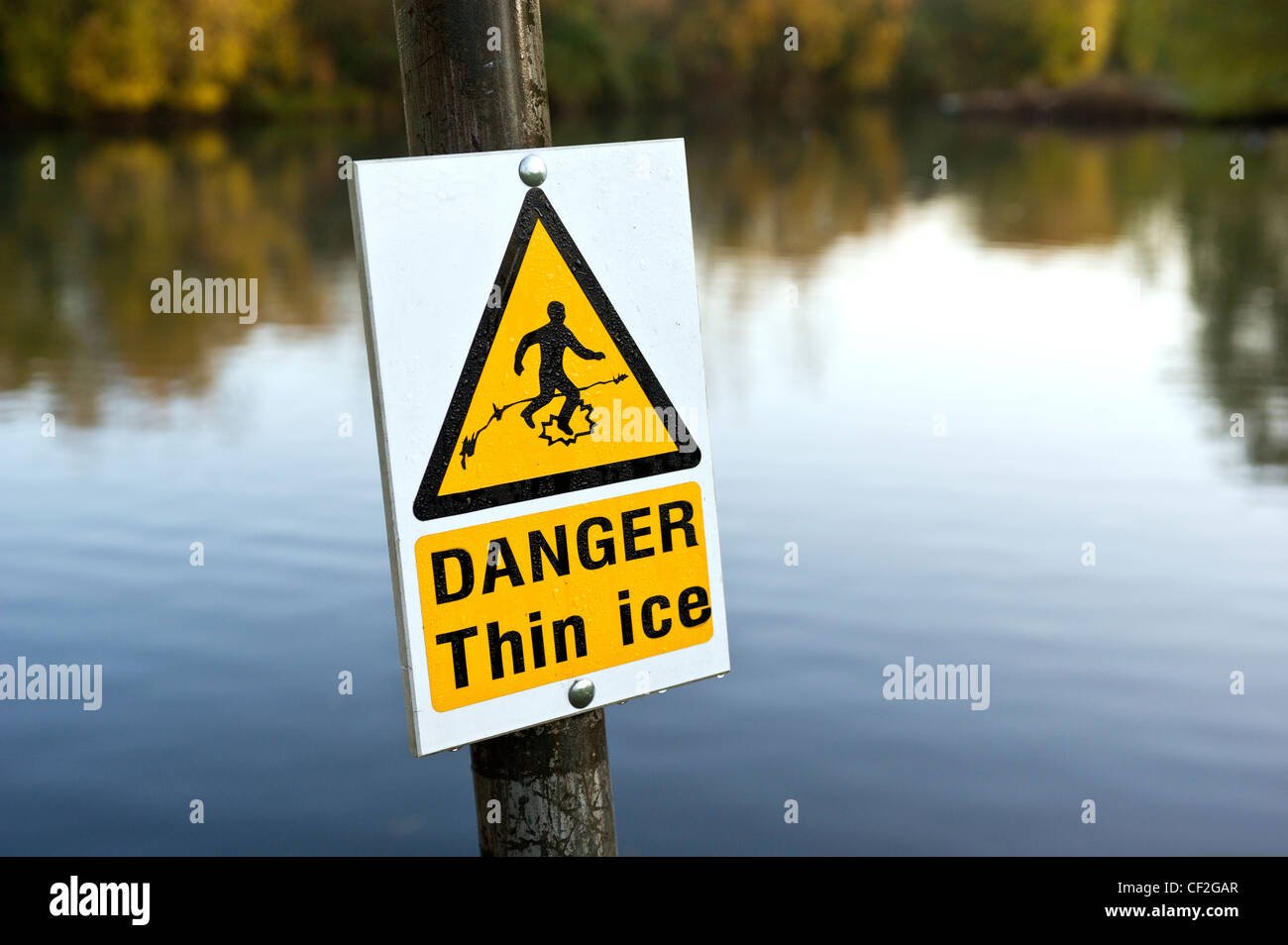 A sign warning about the danger of thin ice. - Stock Image