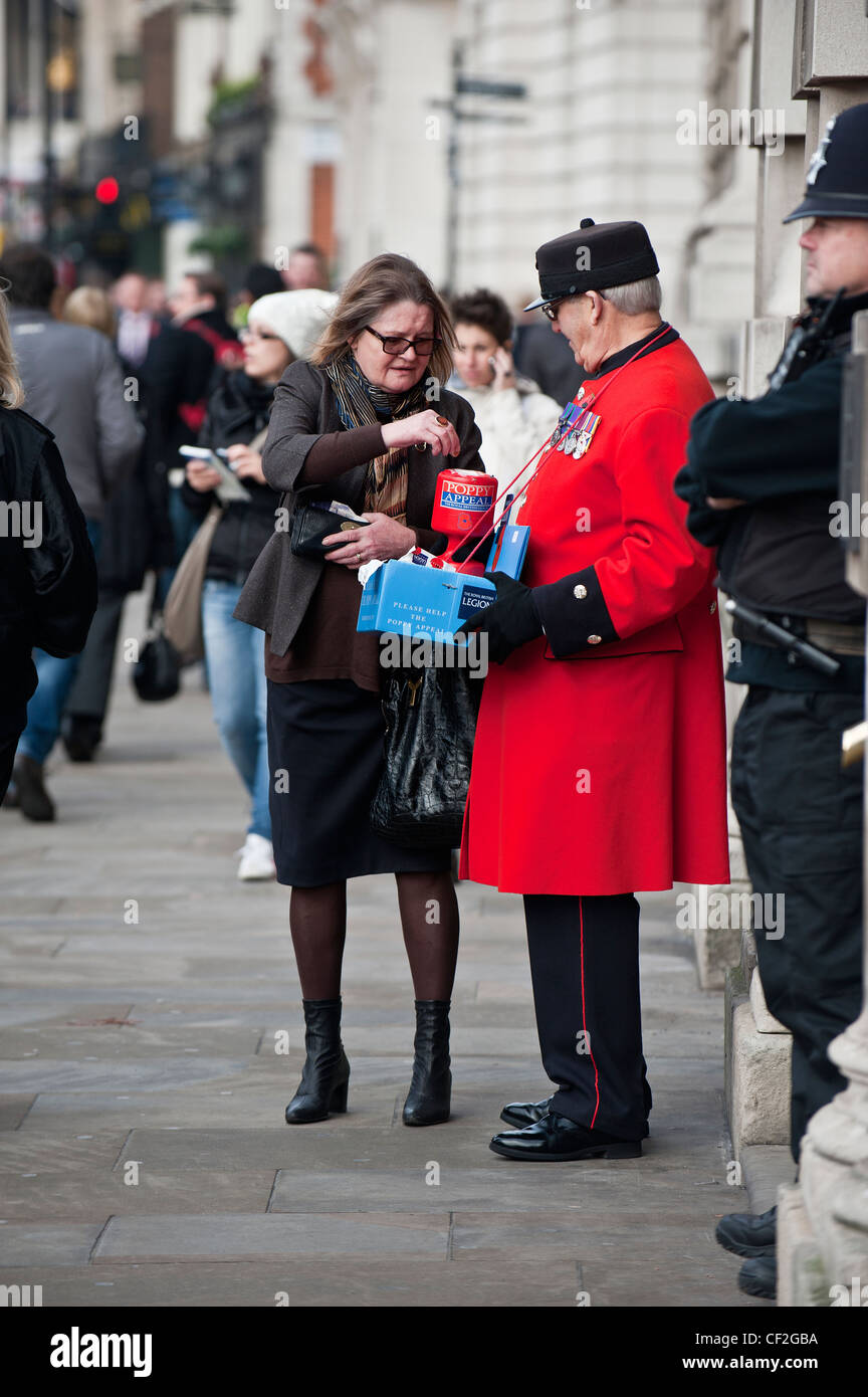 A Chelsea Pensioner raising money for the Royal British Legion by selling poppies. - Stock Image