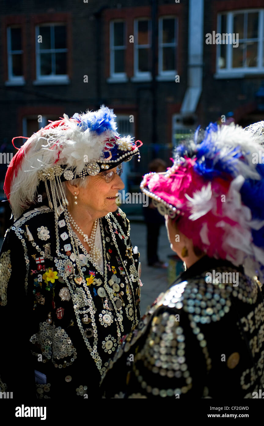 Pearly Queens talking together in Covent Garden. - Stock Image