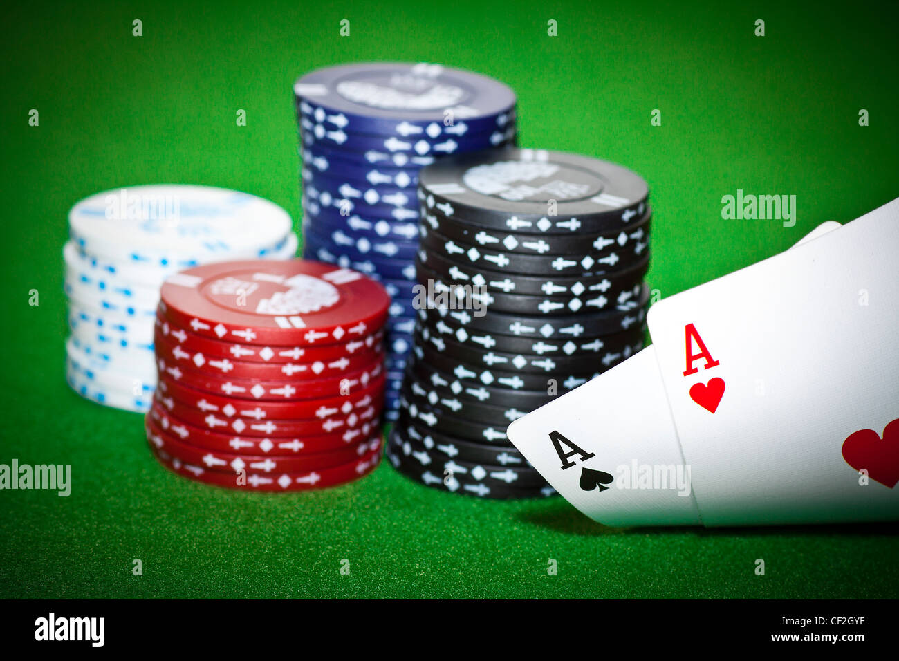 Gambling chips, ace of diamonds and king of spades on green poker cloth. - Stock Image