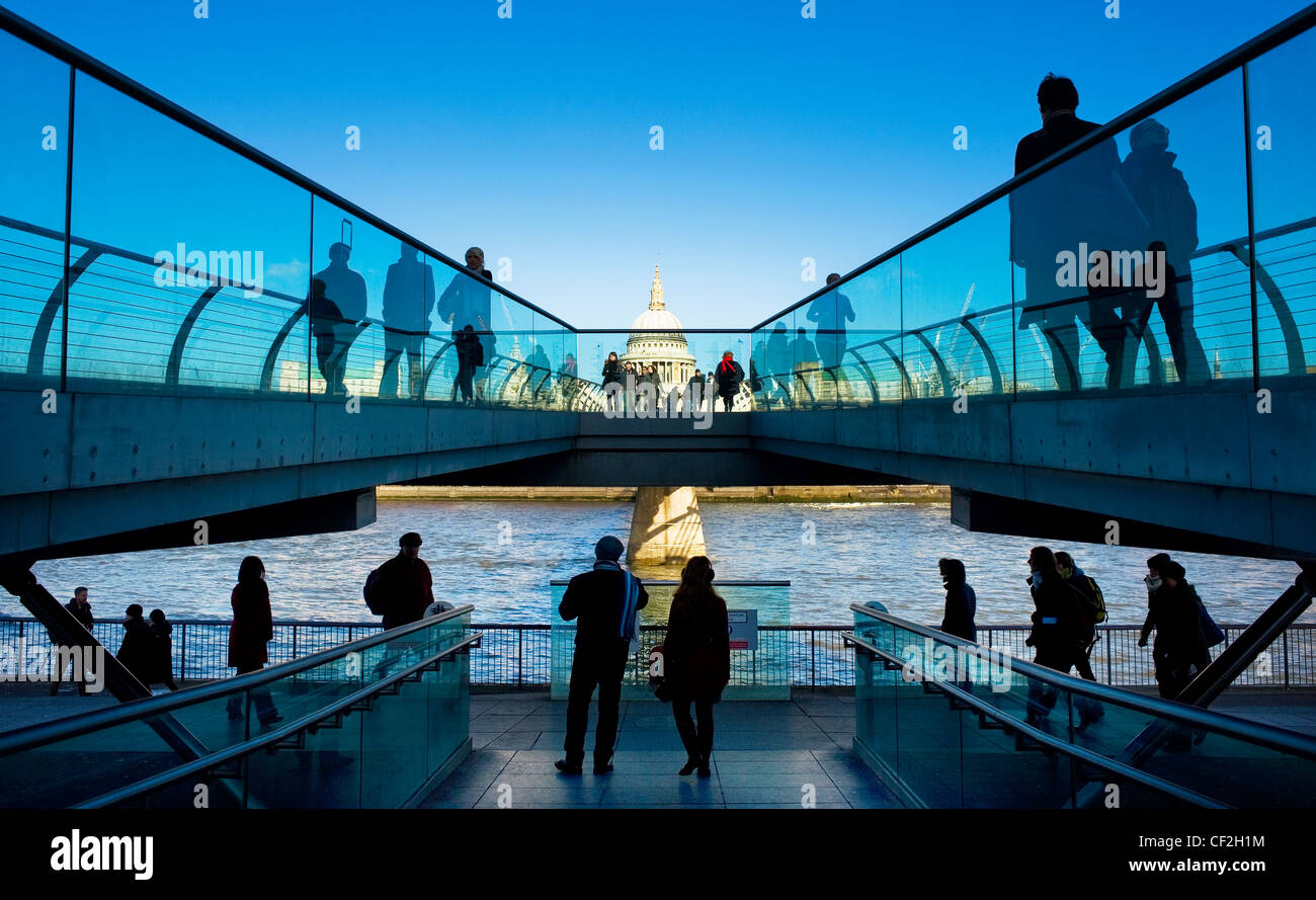 People walking on the Millennium Bridge at Bankside looking towards St Paul's Cathedral on the north bank of the Stock Photo