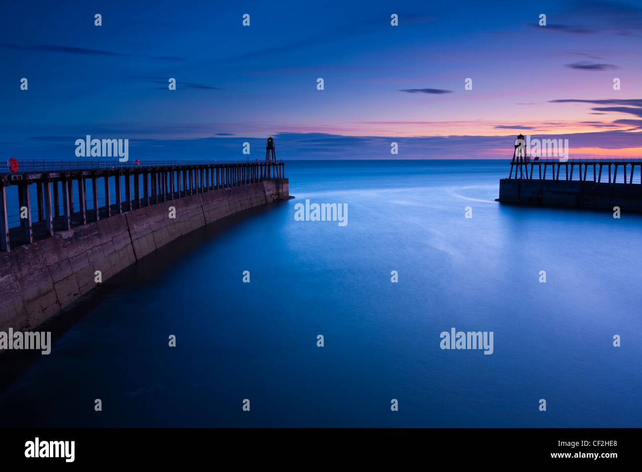 The entrance piers of Whitby Harbour at dawn. - Stock Image