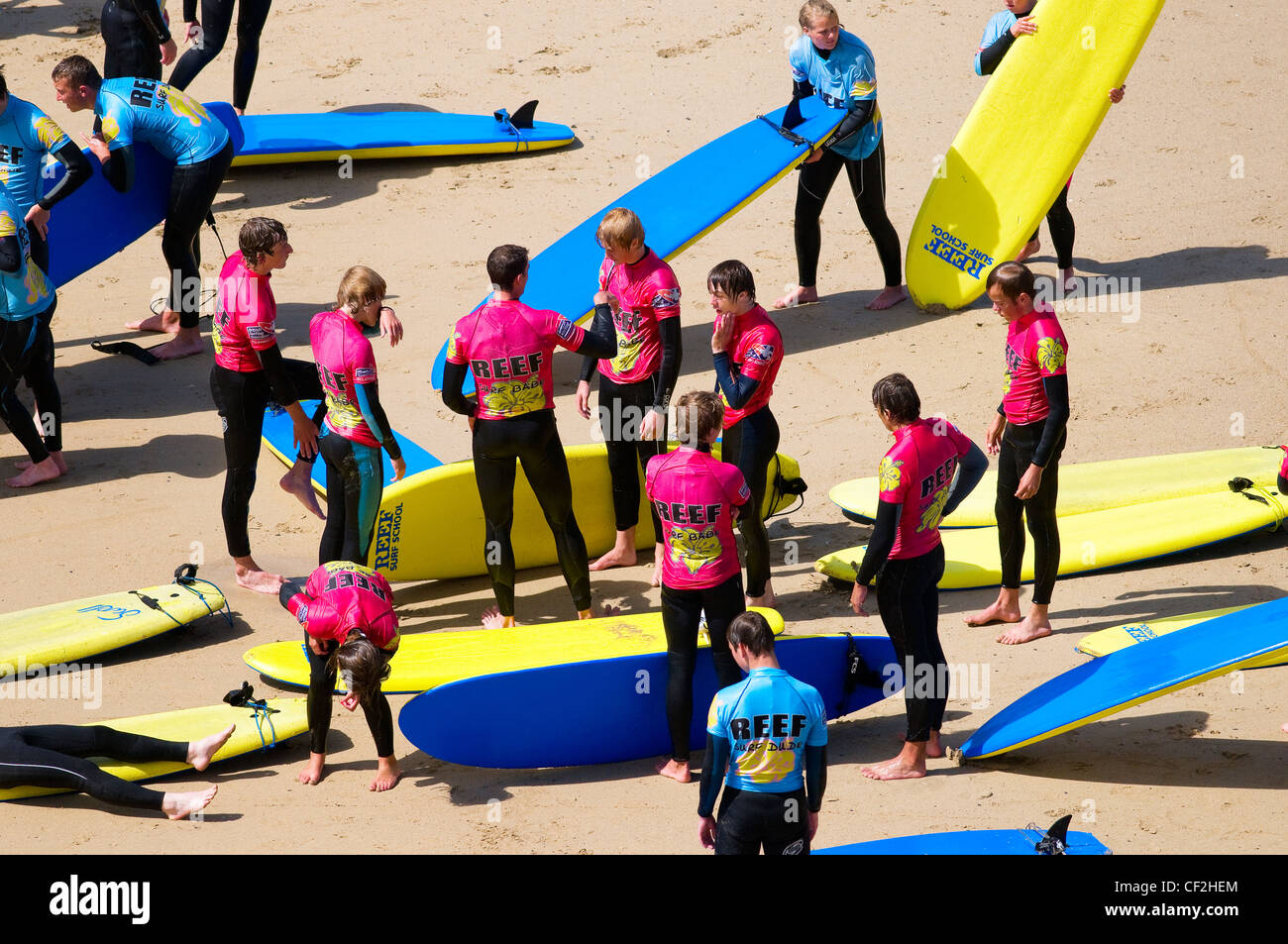 Young people receiving instructions at a surf school on a beach in Newquay. - Stock Image