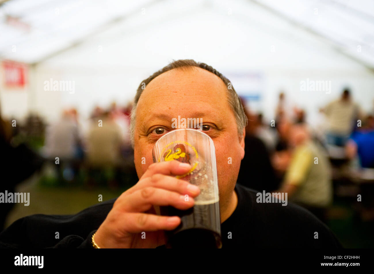 A man drinking a pint of real ale inside a marquee at the Hoop Beer Festival. - Stock Image