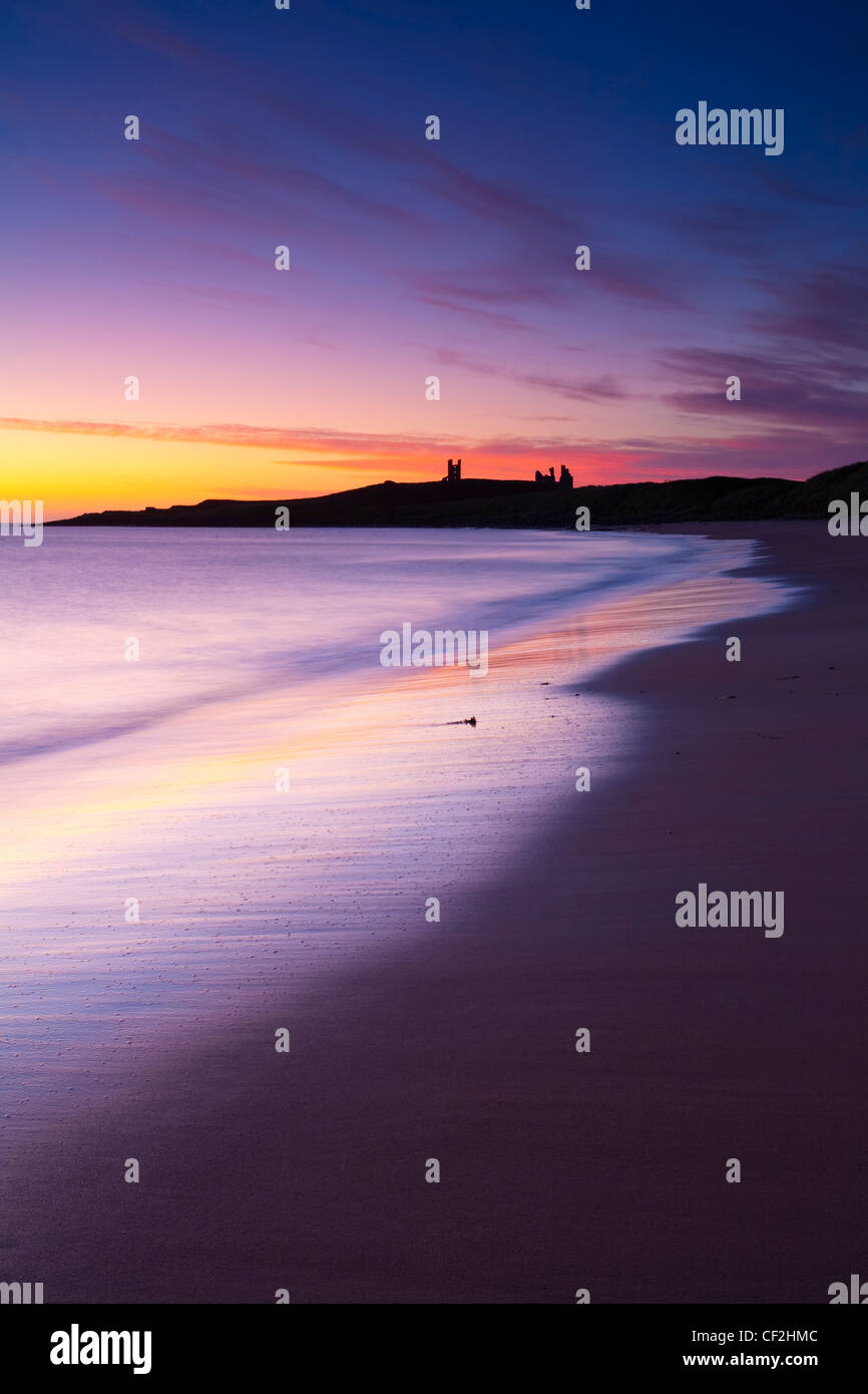 A colourful display of pre-dawn colours relected upon the wet sands of Embleton Bay, overlooked by the dramatic Stock Photo