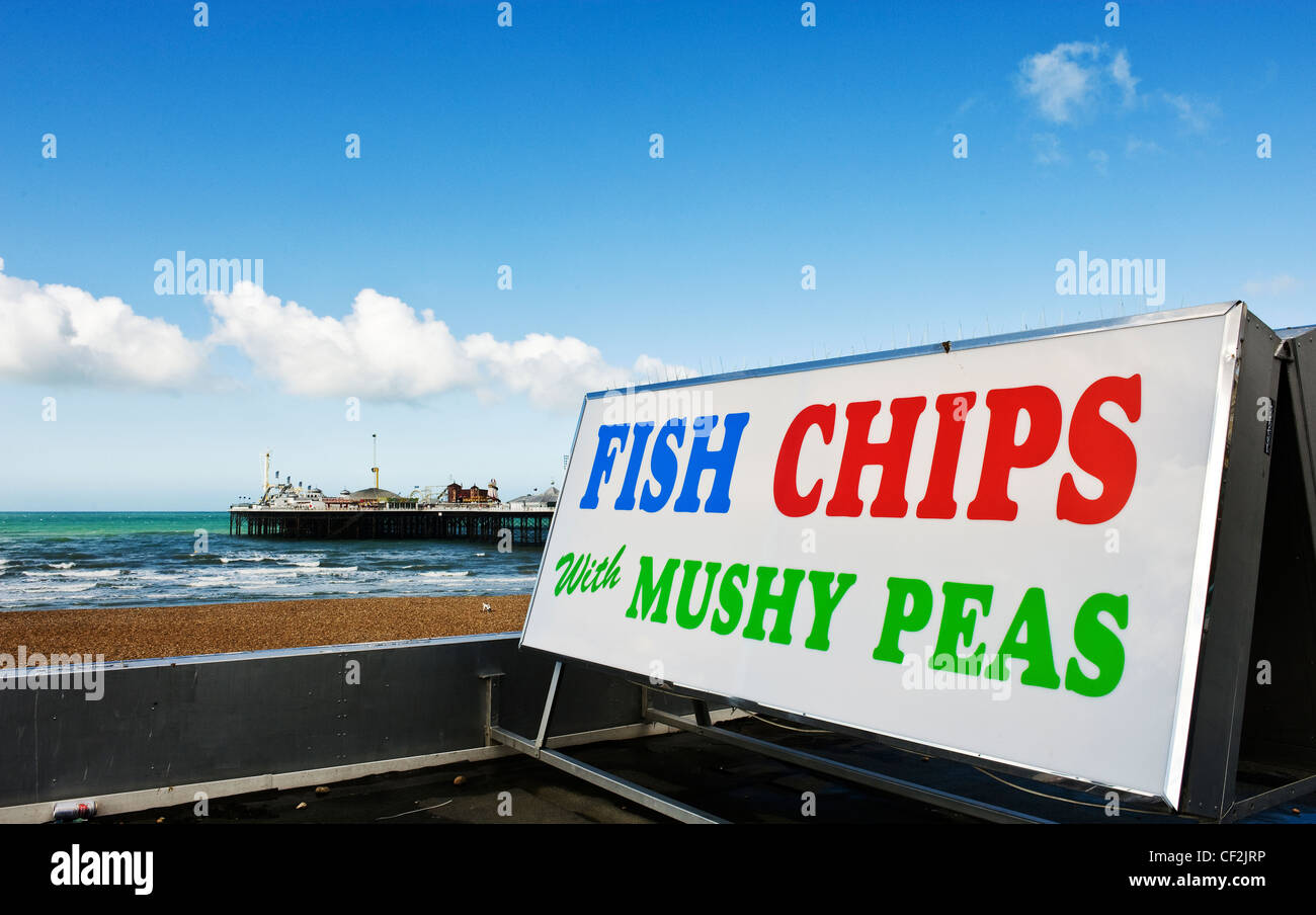 A sign advertising fish and chips with mushy peas on the seafront at Brighton. - Stock Image