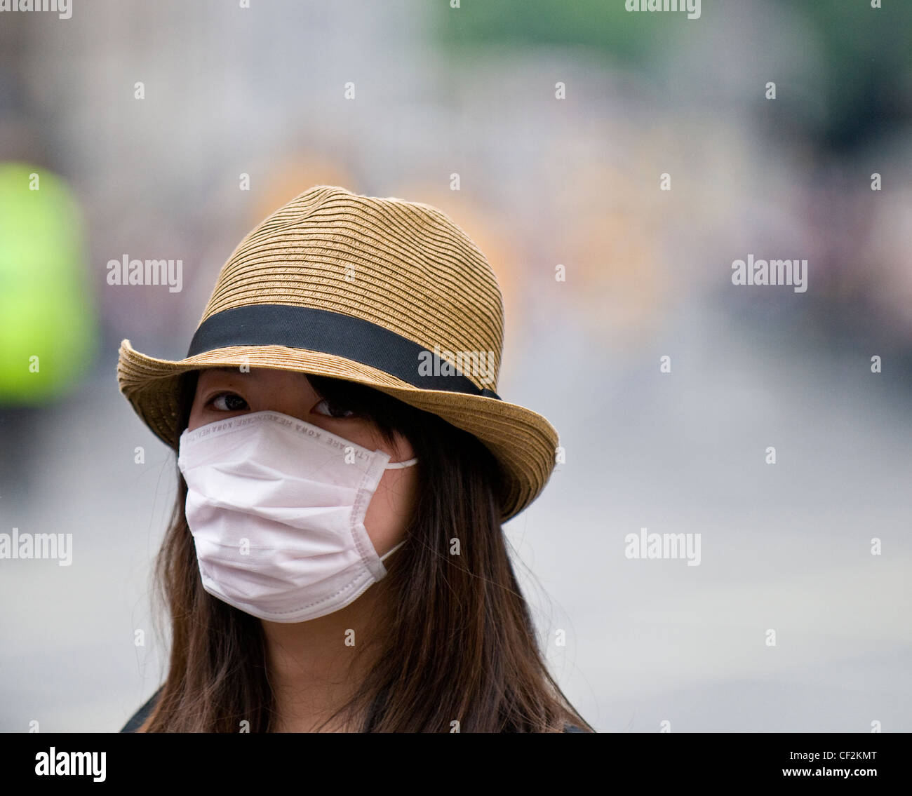 A young woman wearing a face mask to protect herself against catching swine flu. - Stock Image