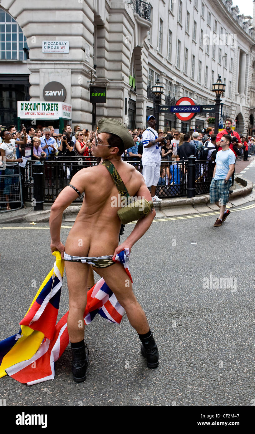 A participant in the Pride London Parade exposing his buttocks. - Stock Image