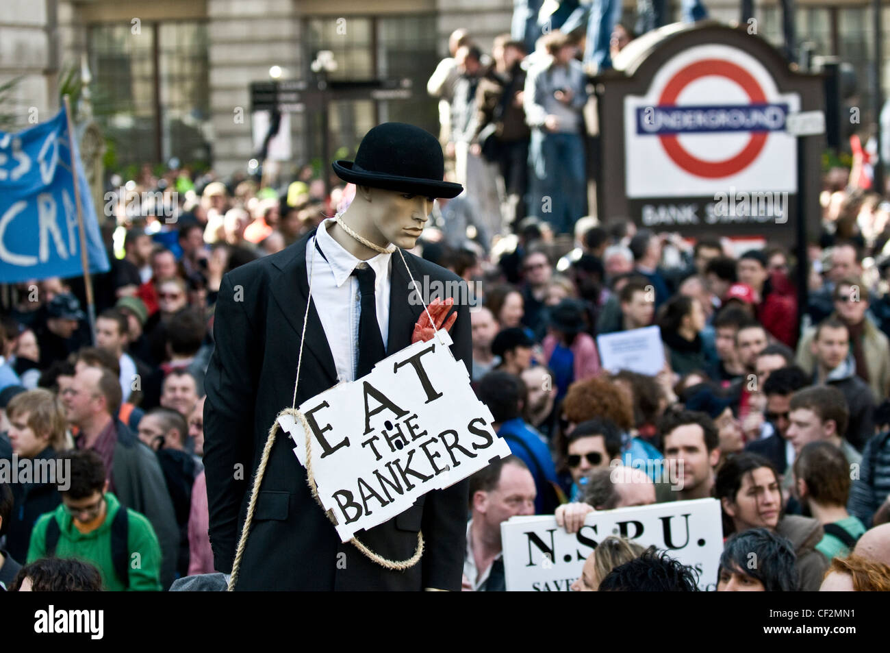 A sign saying 'Eat the Bankers' around the neck of a mannequin dressed in a suit at the G20 demonstration - Stock Image