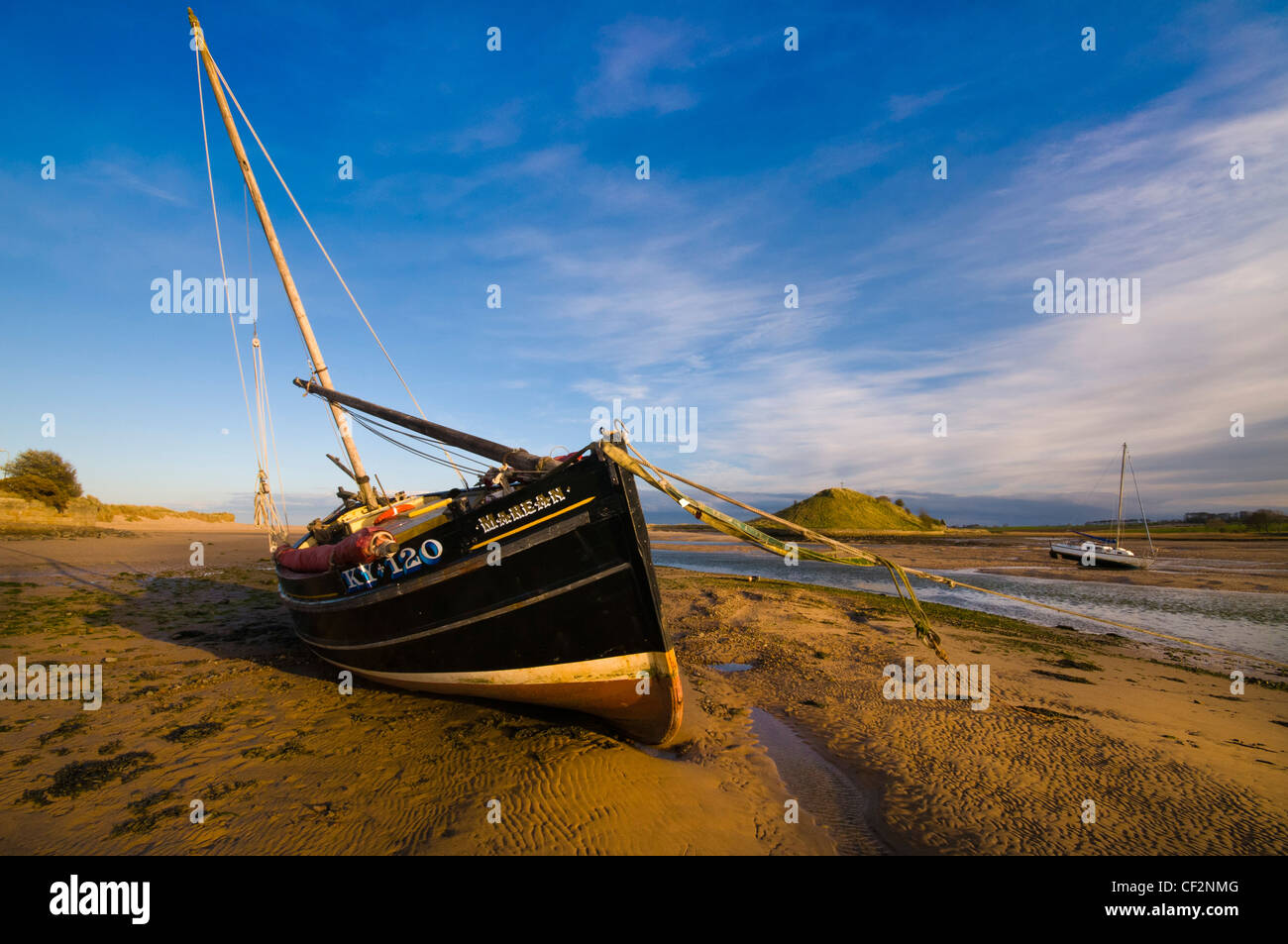 A sailing boat beached in the River Aln estuary at Alnmouth on the North East coast of England looking towards Church - Stock Image