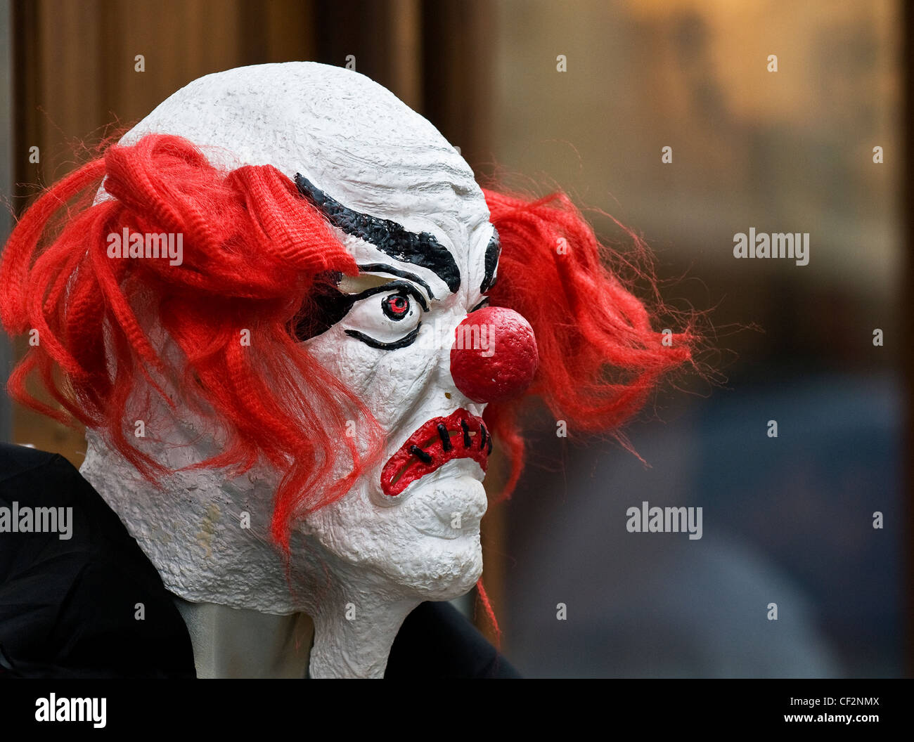A frightening clown mask on a dummy. - Stock Image