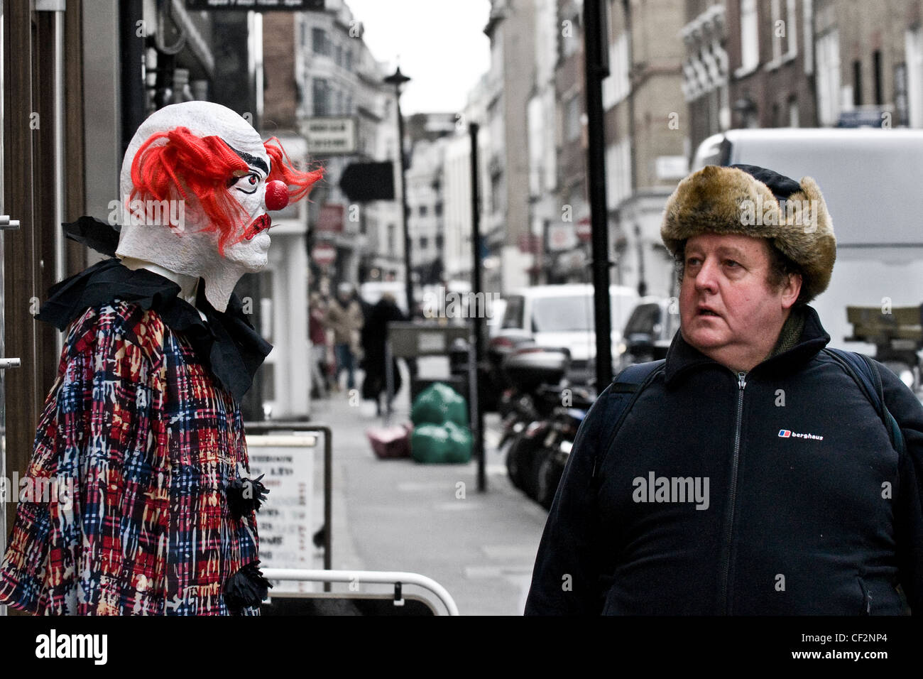 A pedestrian looking at a dummy dressed as a frightening clown. - Stock Image