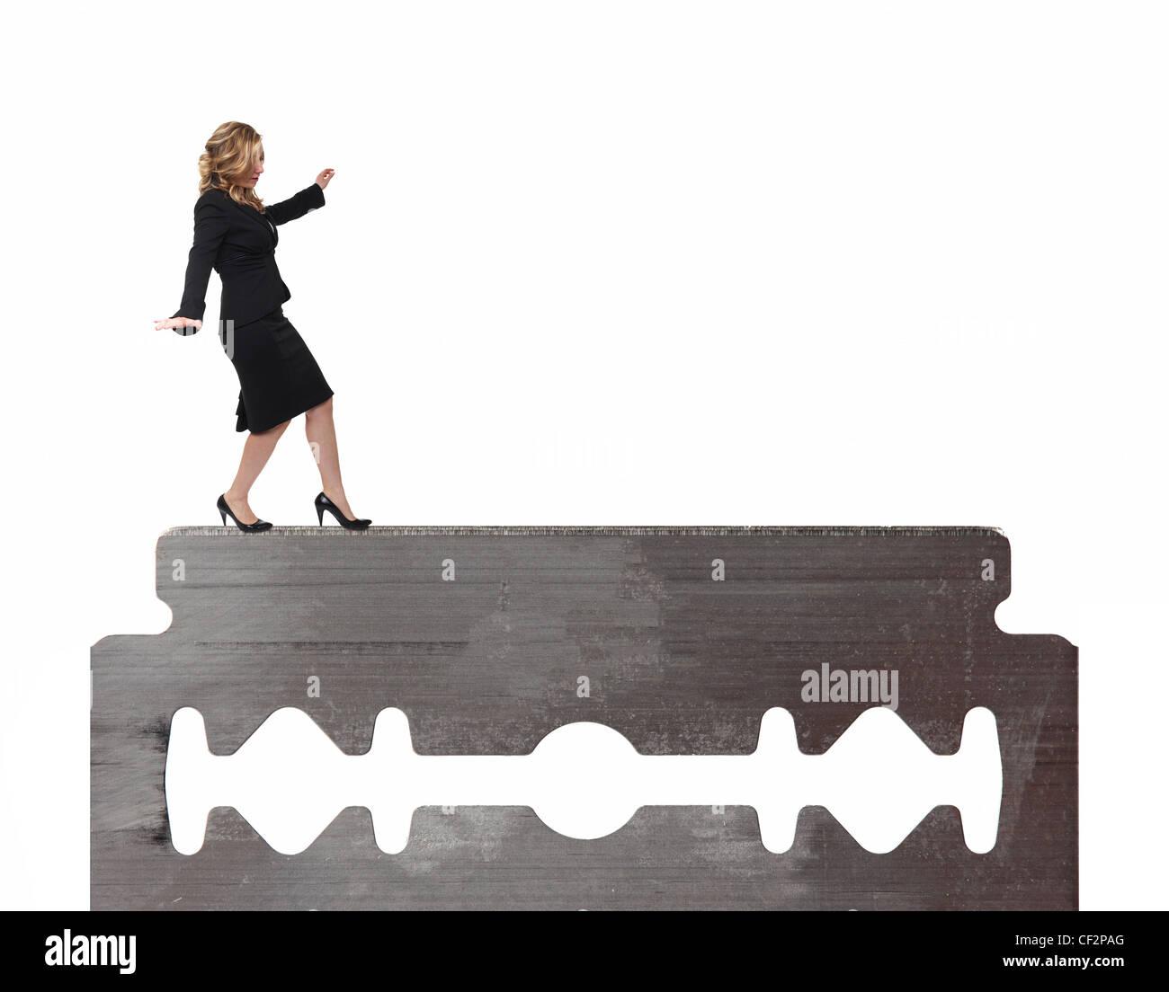 businesswoman walk on razor blade - Stock Image