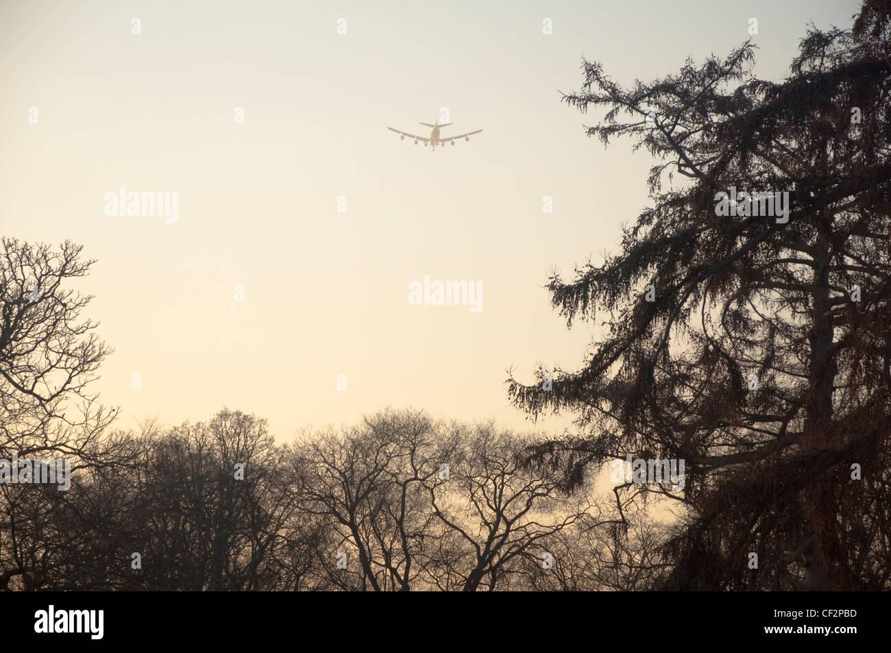 Aeroplane flying over Kew Gardens at dusk - descending towards Heathrow Airport. London, UK. - Stock Image