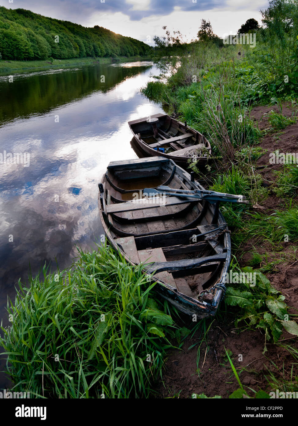 Old fishing boats on the riverbank of the River Tweed. - Stock Image