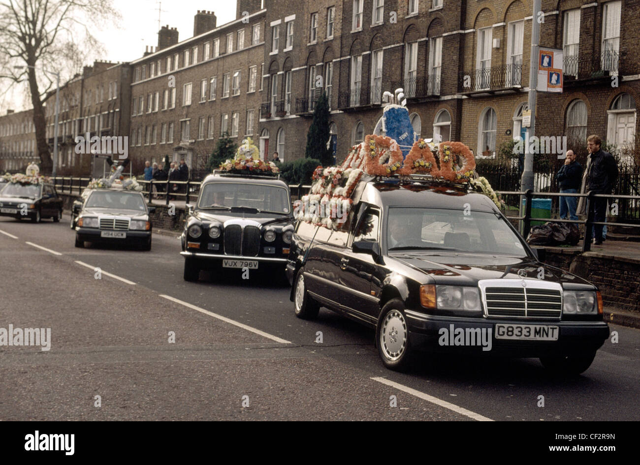 Procession Of Funeral Cars Laden With Flowers On The Roof Follow The