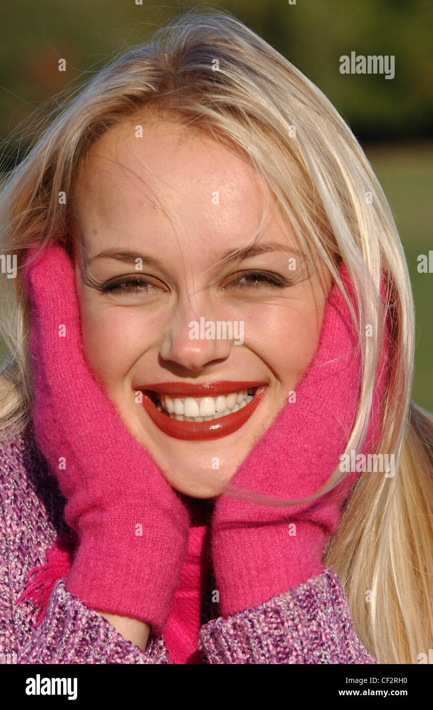 Female long blonde hair brown tones of make up wearing purple jumper bright pink scarf and mittens holding face - Stock Image