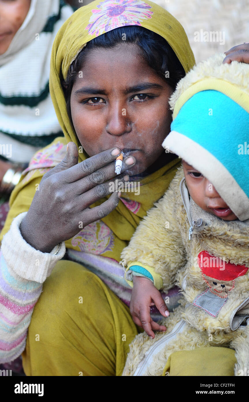 Woman smoking beside a child - Stock Image