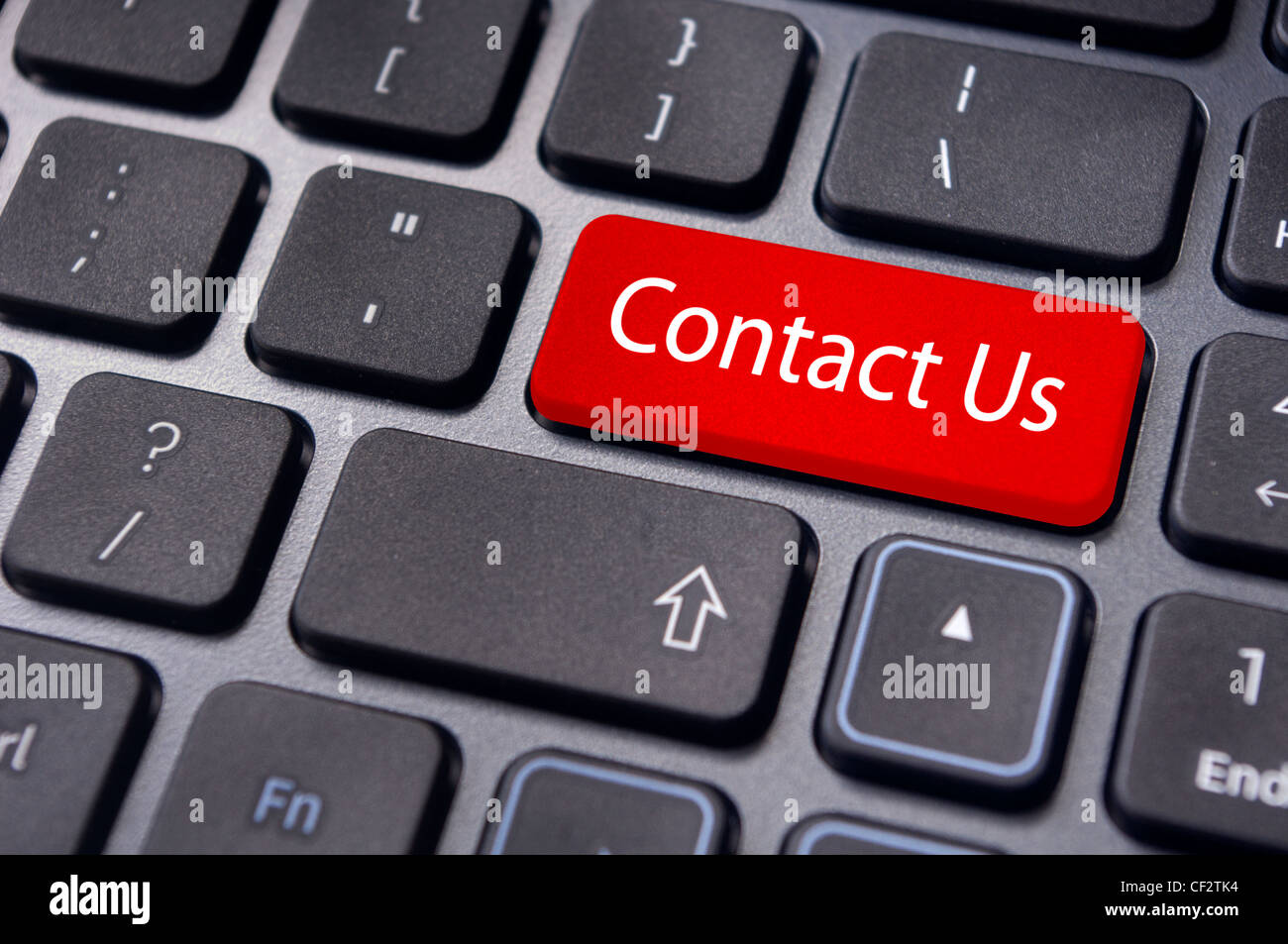 A 'contact us' message on enter key of keyboard, for online communications. - Stock Image