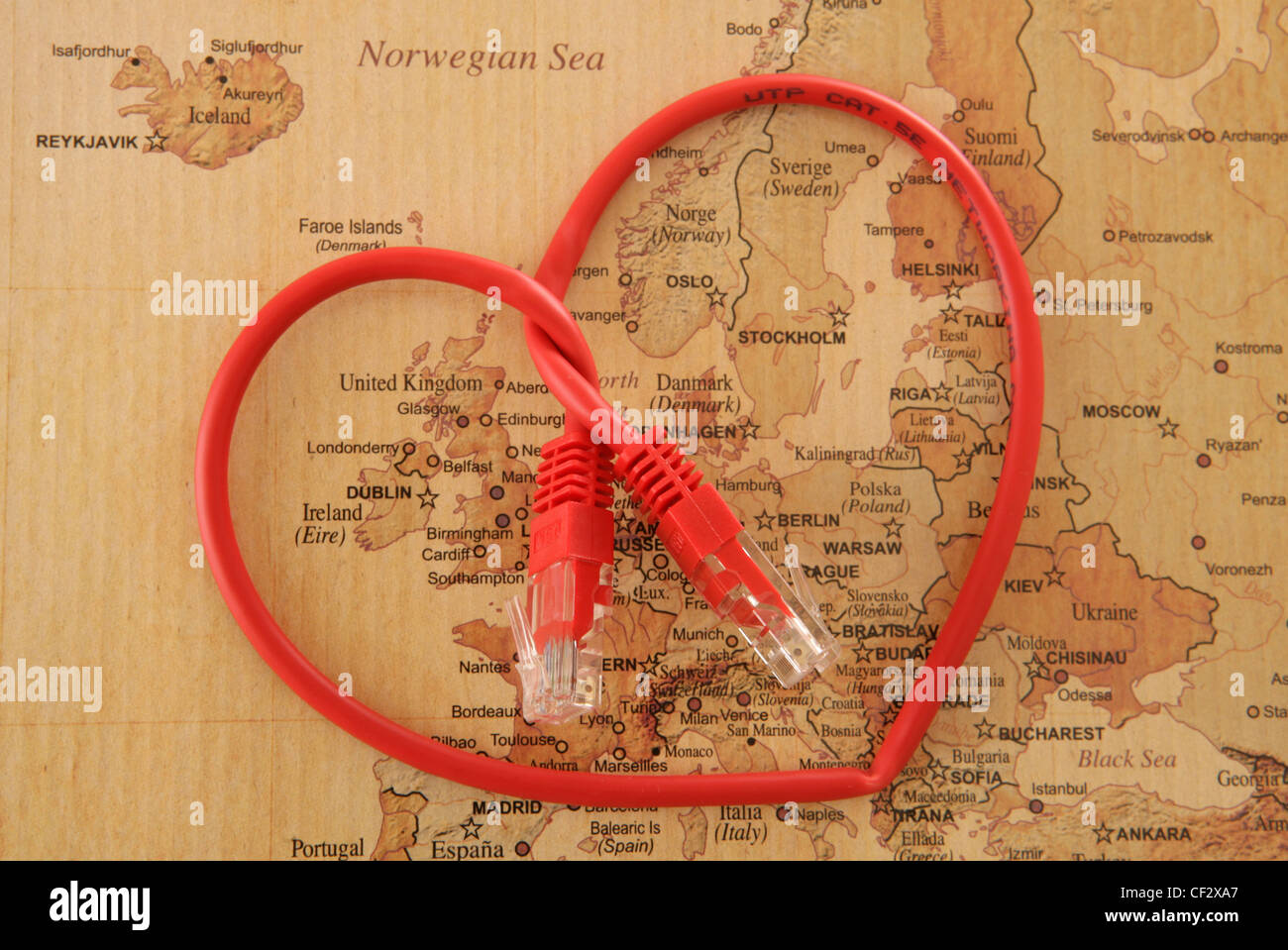heart shape cable on vintage map of Europe in studio - Stock Image