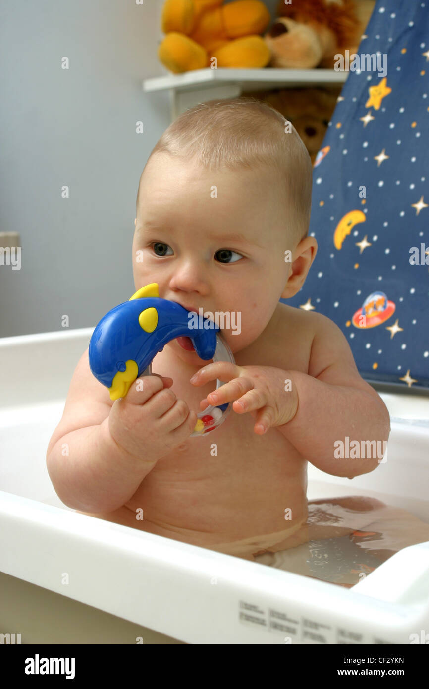 Male baby sitting in bath holding teething ring in his mouth Stock ...