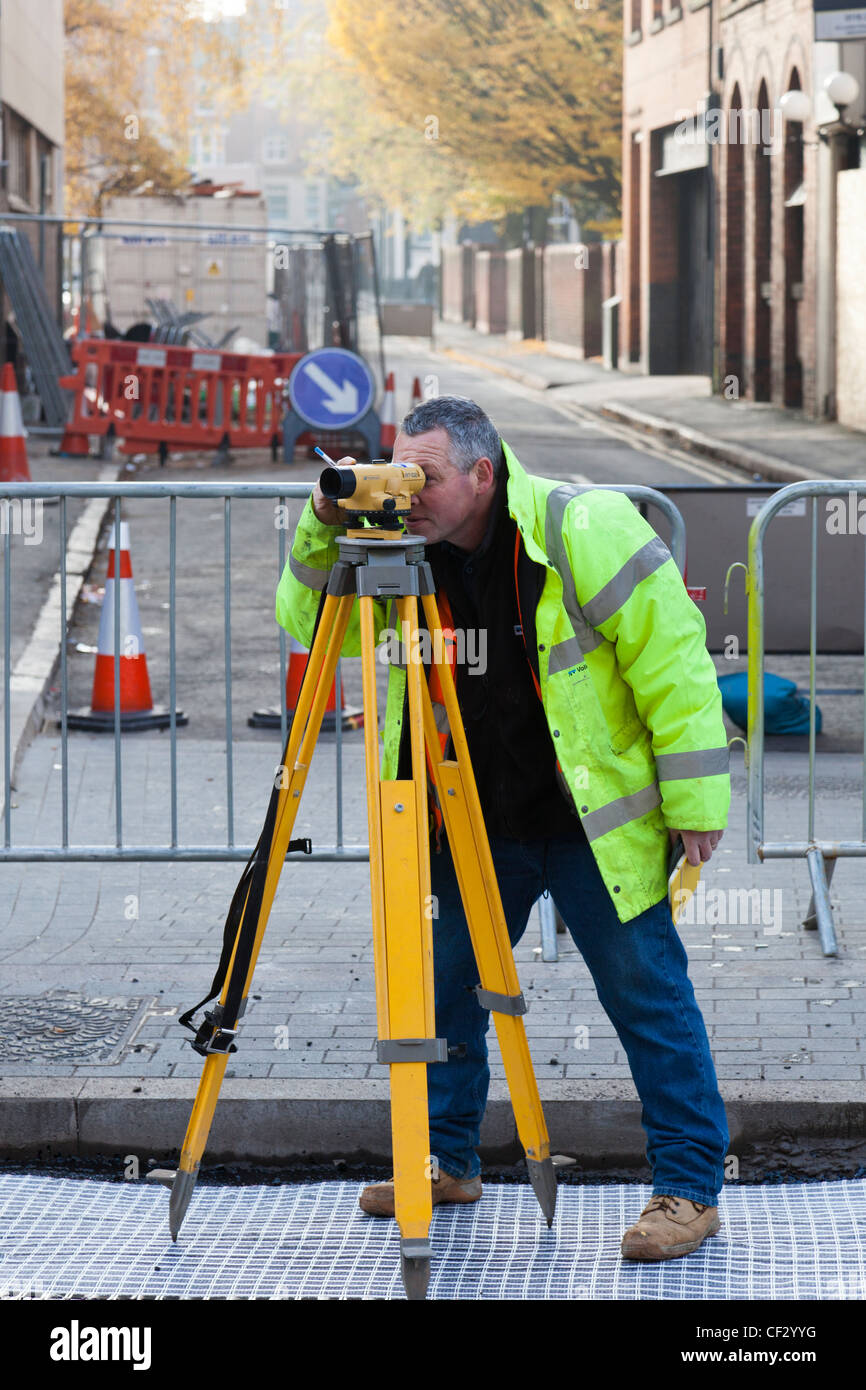 Surveyor uses a theodolite to set levels for roadworks. - Stock Image