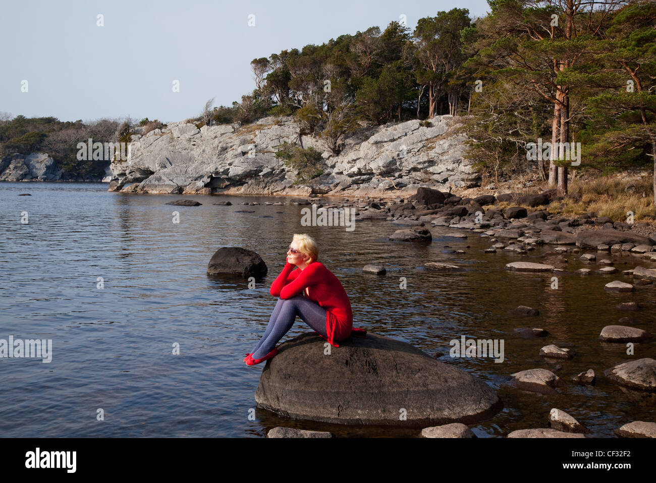 A Young Woman Sits On A Large Rock On Muckross Lake; Killarney County Kerry Ireland - Stock Image