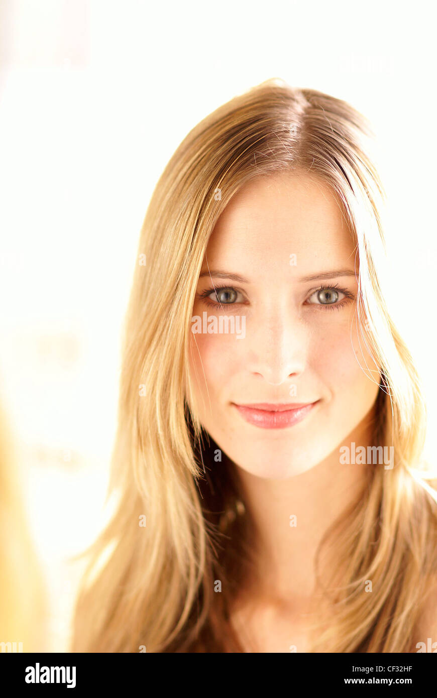 Female with long blonde hair worn loose, clear fair skin, wearing natural make up, looking at the camera and smiling - Stock Image