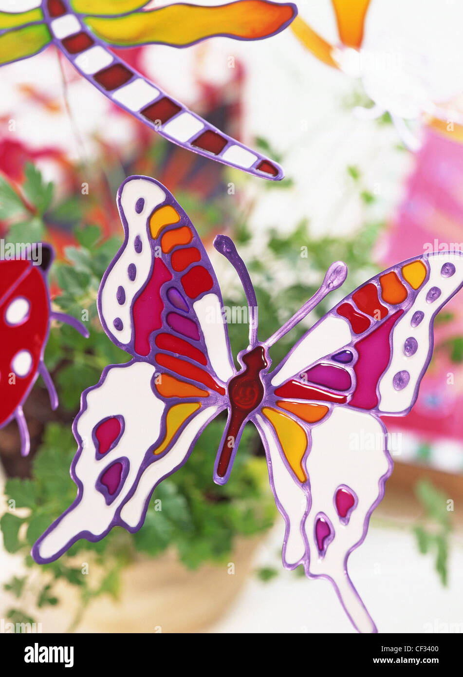 Glass glaze creations Turn ordinary articles into works of art colourful glass glaze Butterfly design pot plant - Stock Image