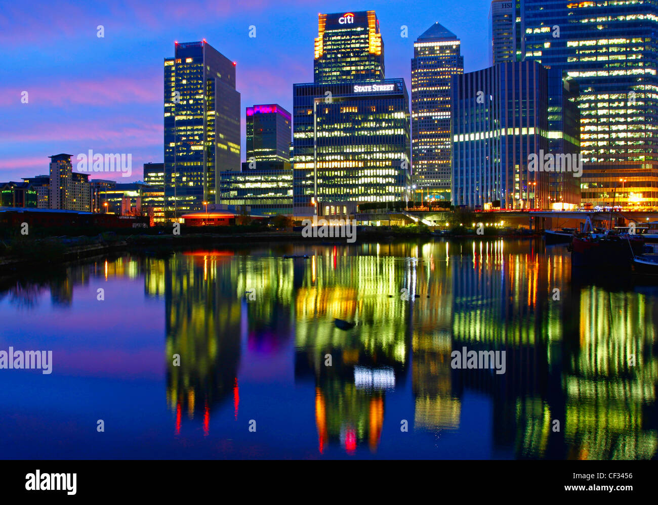Lights from skyscrapers in Canary Wharf reflected in Blackwall Basin at night. - Stock Image