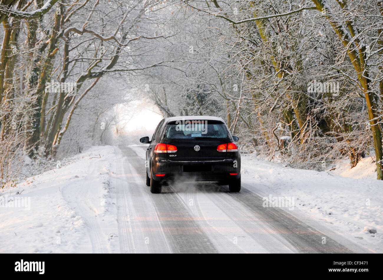 VW Golf car driving on snow covered road (obscured numberplate) - Stock Image