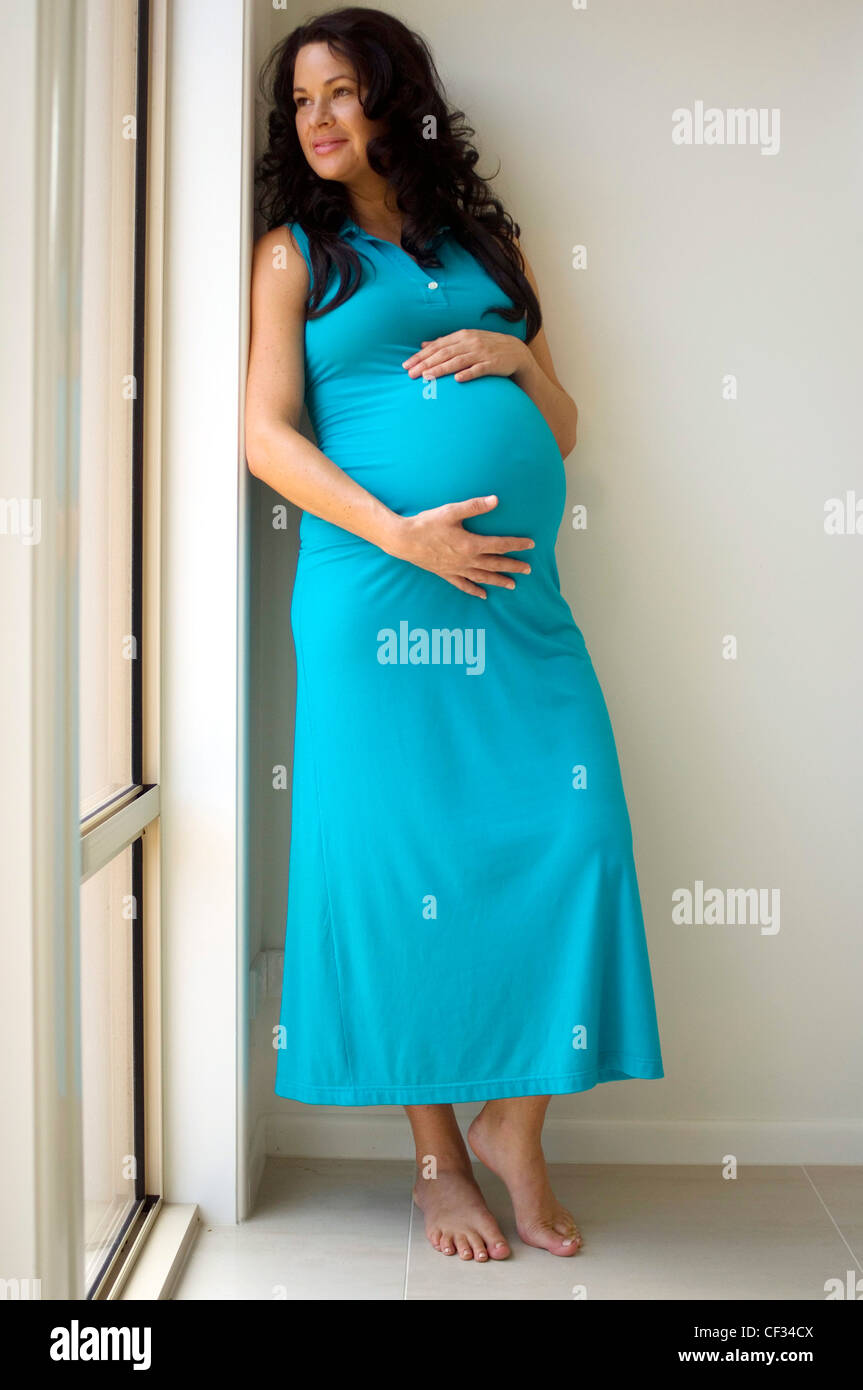 Pregnant female with long curly brunette hair, turquoise blue Stock ...