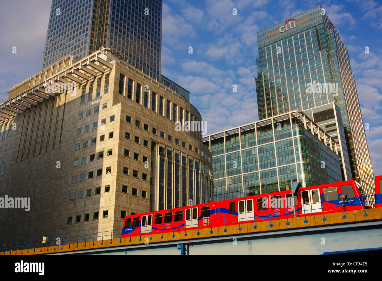 A Docklands Light Railway (DLR) train travelling past the skyscrapers and buildings at Canary Wharf. - Stock Image