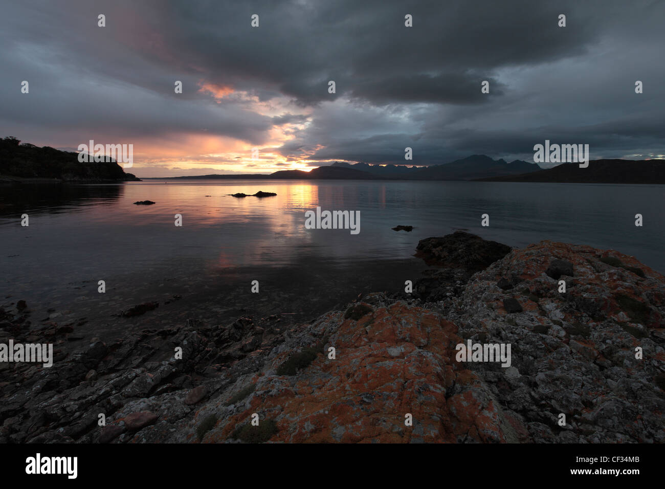 View across Loch Eishort towards the sunsetting behind the Cuillin hills on the Isle of Skye. - Stock Image