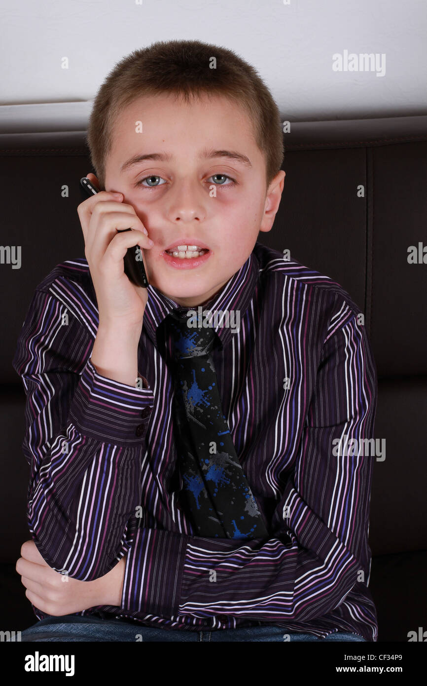 Young boy talks on his mobile phone while sitting on the sofa. - Stock Image