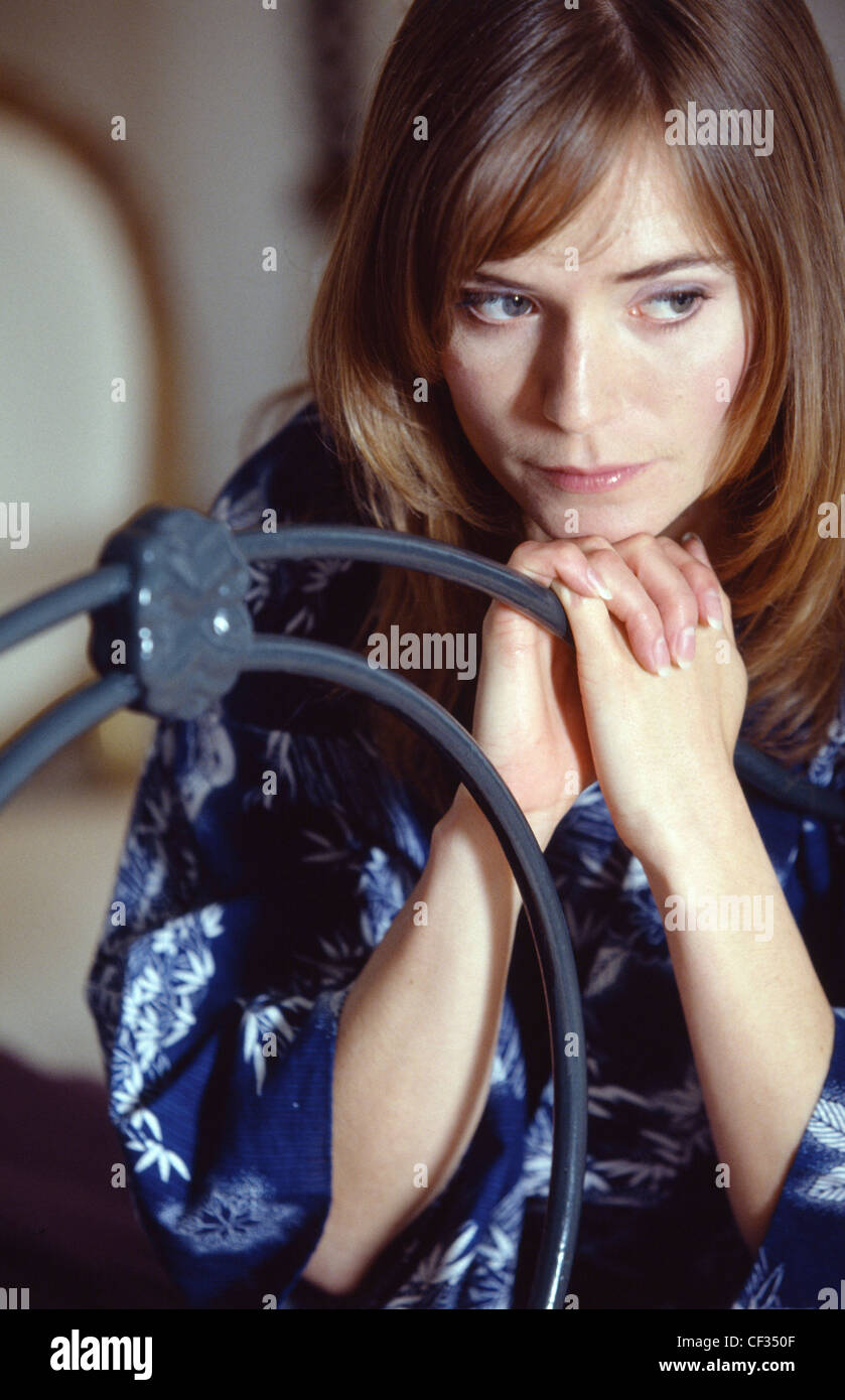 Female wearing dressing gown sitting on end of bed leaning on frame Stock Photo