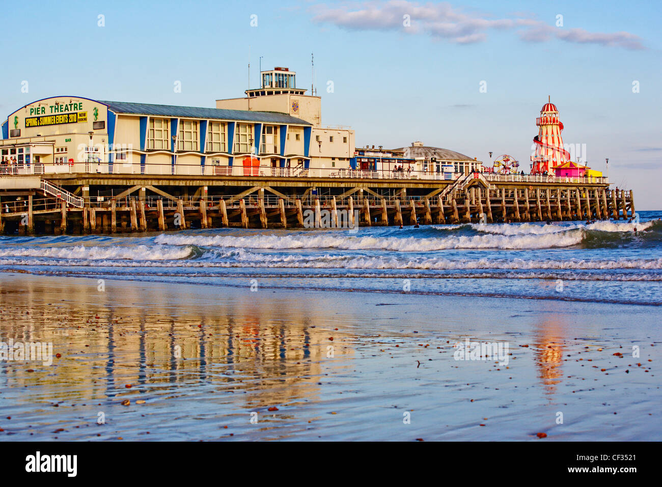 Waves rolling onto the beach past Bournemouth Pier. - Stock Image