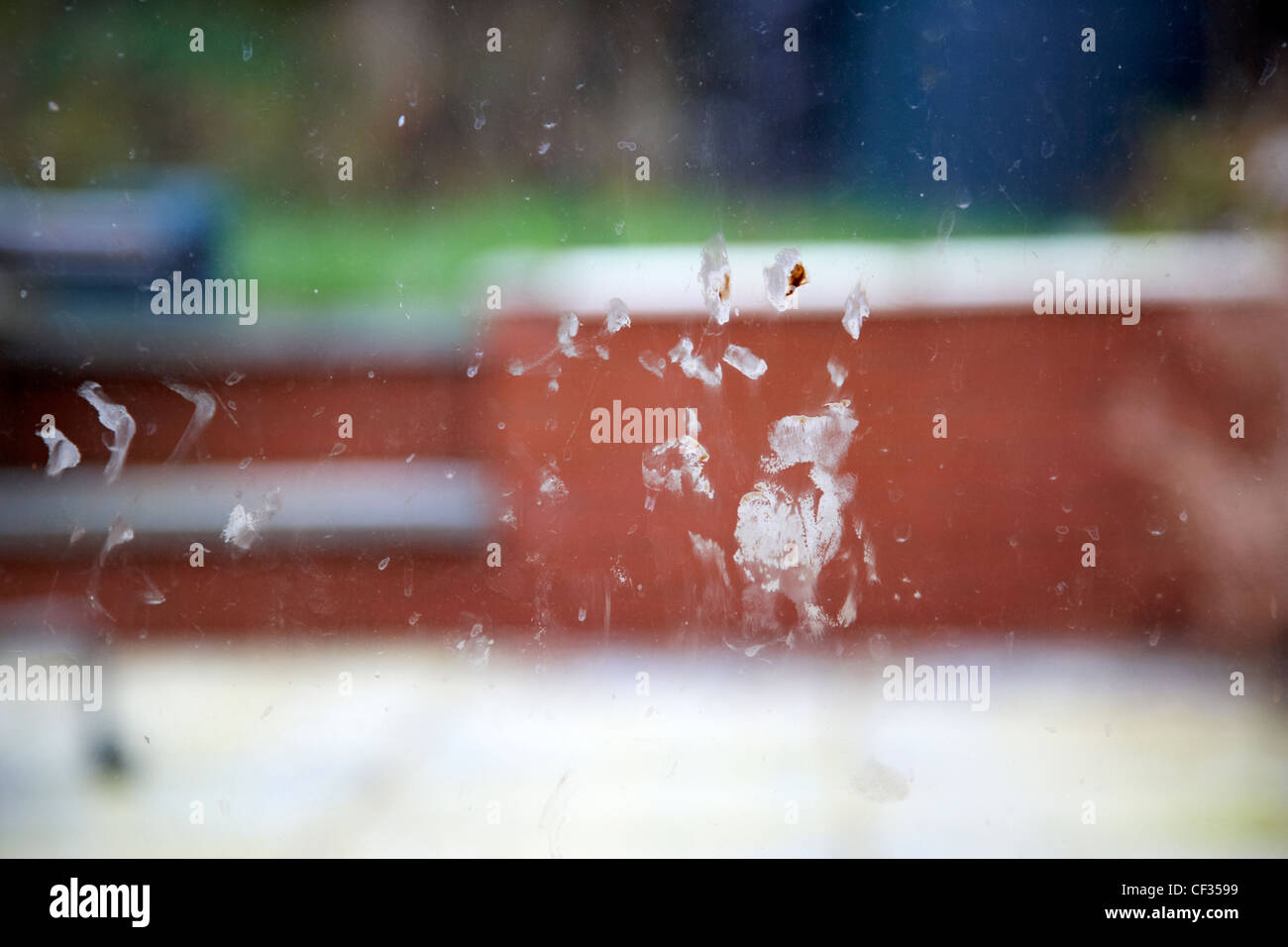 childs handprint in chocolate on dirty house window looking out to garden - Stock Image
