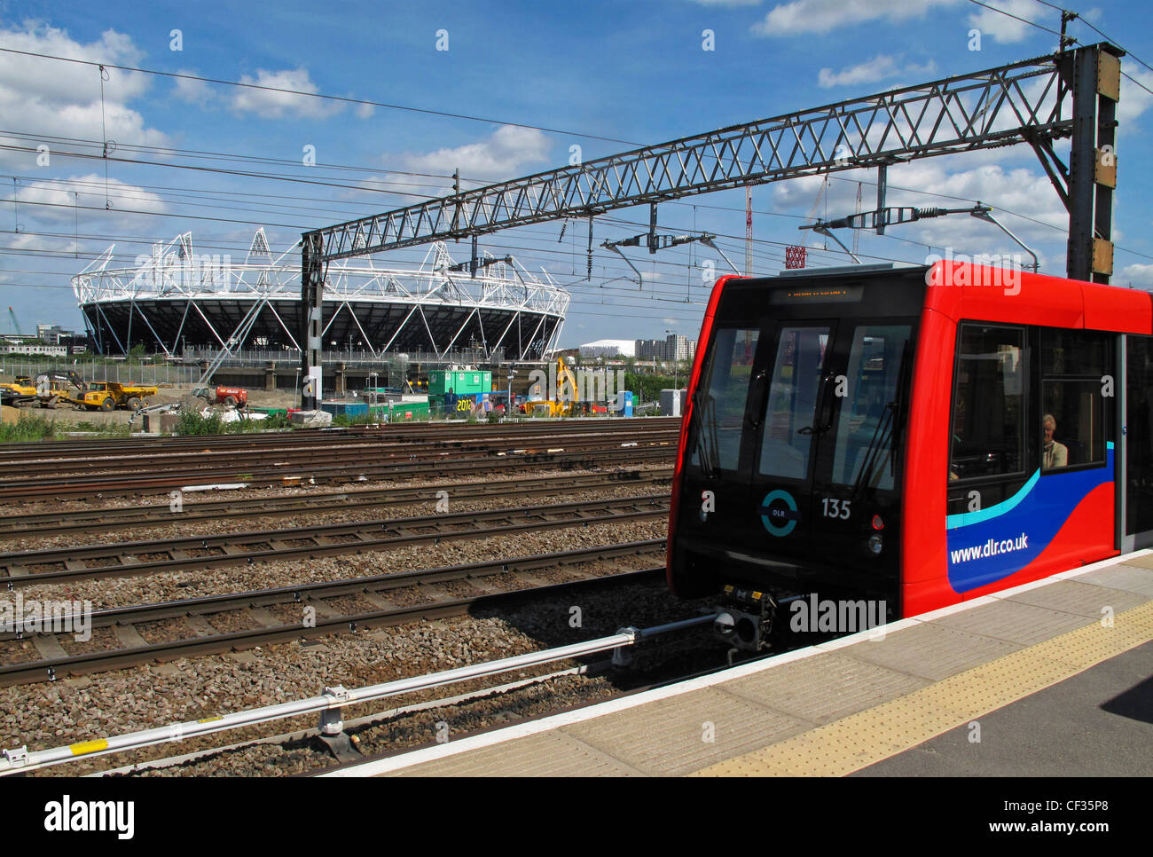 A Docklands Light Railway train alongside a platform with the Olympic Stadium in the background. - Stock Image