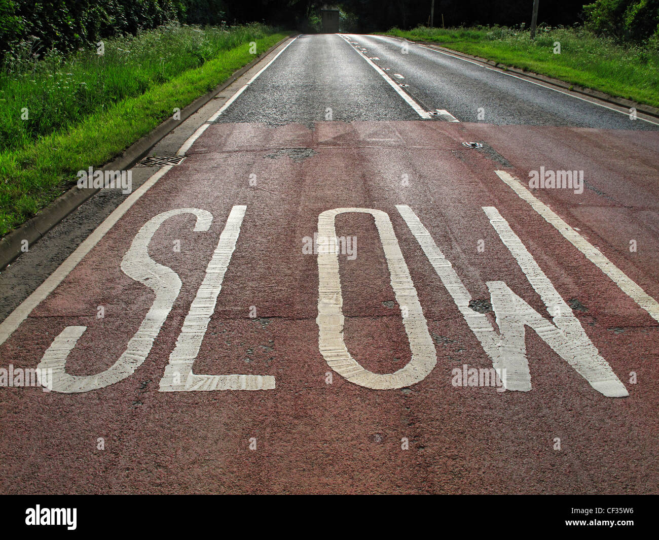 Slow warning sign written on the surface of a rural English road. - Stock Image